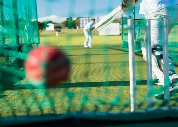 Bowler and batsman in cricket nets