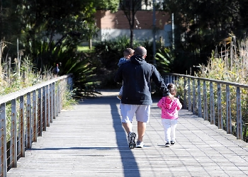 Father walking children across pedestrian bridge, rear view