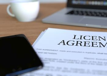 Licence agreement and mobile phone in front of a laptop
