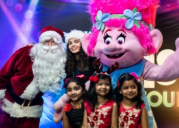 Santa Claus and local community members with a pink haired female Troll at Christmas celebration