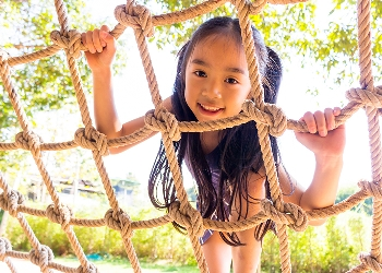 Girl playing on climbing net rope at playground