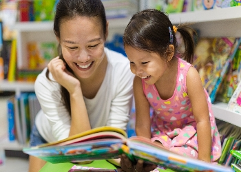 Mother and daughter reading books in library